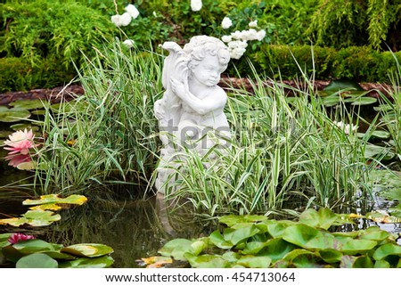Background of garden design. Landscaping in park with pond, boy angel statue and lotus flowers - stock photo