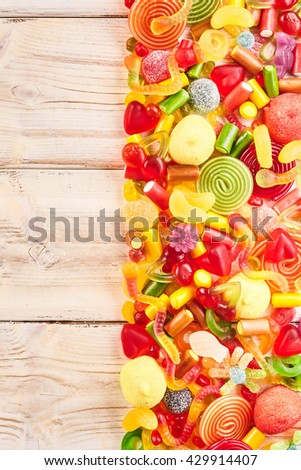 Background of half filled wood table with candies, licorice rolls, fruit flavored gummy slices and other yummy confections