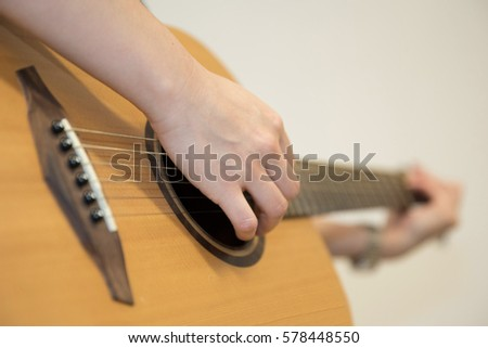 background of hand playing guitar