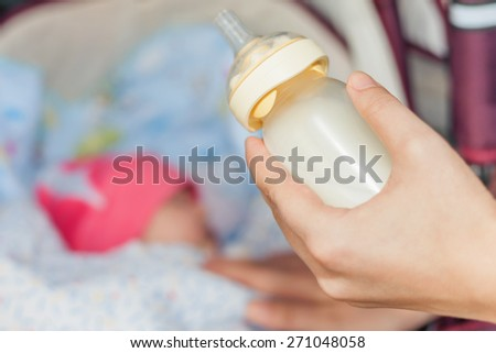 background of happy mom holding at hand baby bottle with milk at foreground