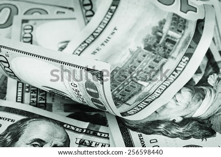 Background of hundred-dollar bills and one twisted top stained in green tone - stock photo