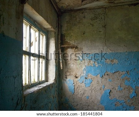 Background of image desolate old industrial building blue painting abandoned room inside Natural day light in wooden window frame  - stock photo