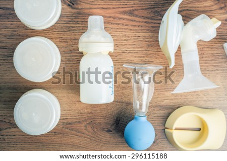 Background of manual and automatic breast pump, baby bottle with milk. Mothers breast milk is most healthy food for newborn baby - stock photo
