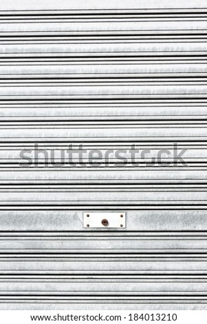 background of metallic roller shutter with door lock - stock photo