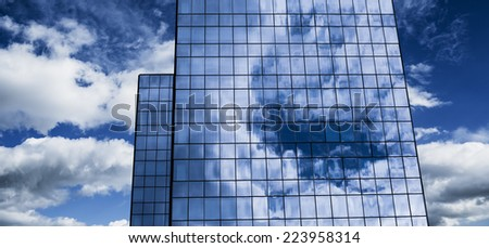 Background of modern office building. Clouds reflected in windows. Color toned image. - stock photo
