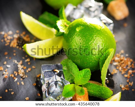 Background of Mojito cocktail ingredients on a table in summer bar, Alcohol cocktails with Rum, lime, mint, ice cubes and brown sugar closeup, Party drink. Isolated on black background - stock photo