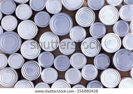 Background of multiple sealed food cans or tins viewed from overhead in an assortment of sizes filling the frame in a food and nutrition concept - stock photo