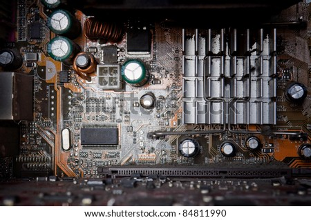 background of old electronic circuit boards in dark colors - stock photo
