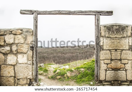 background of Old empty door frame with stone fence texture backdrop with gray sky and spring fresh green grass on hill  - stock photo