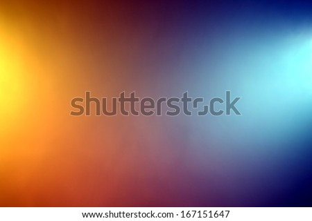 Background of orange and blue color lights shining through fog