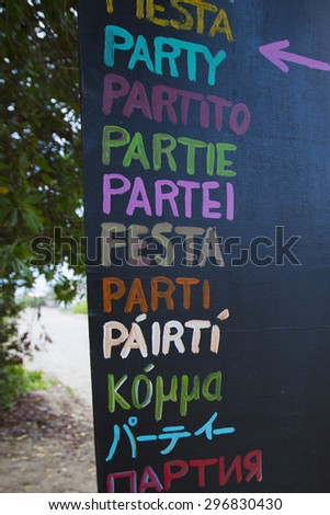 Background of party sign written in various languages and different colors on wooden board on the beach. Galapagos Islands. Ecuador 2015 - stock photo