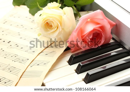 background of piano keyboard with roses - stock photo