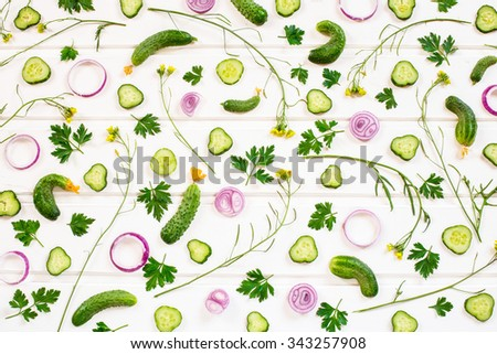 Background of raw cucumber, onion, parsley and arugula yellow flowers on the white wooden table. - stock photo