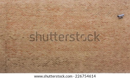 Background of red bricks wall with a surveillance camera in one hand - stock photo