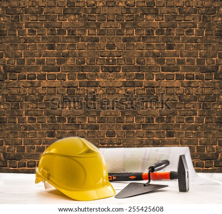 background of  red brown brick texture wall space Industrial construction tools yellow hardhat stand Blue print yellow plastic Helmet paper blueprint document trowel and hammer lie on table - stock photo