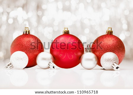 Background of red Christmas baubles with a bokeh of sparkling festive party lights and copyspace for your seasonal greetings - stock photo