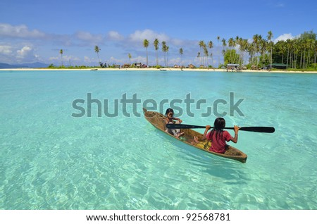 Background of seascape with children rowing boat on clear water, at Semporna, Sabah in Malaysia