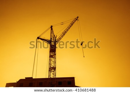 Background of silhouette building crane lift loads with sun set rays yellow cloudy evening sky backdrop. Construction site at orange sunset - stock photo