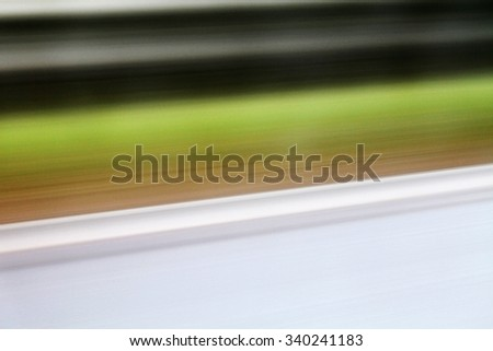 Background of stripes in blurred motion - black, green, white, brown.