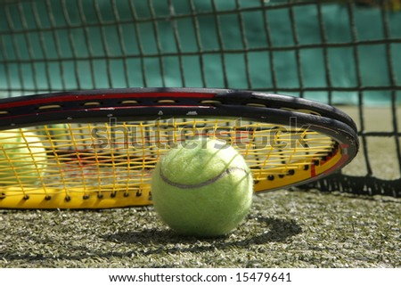 Background of tennis ball and racket in front of net - stock photo