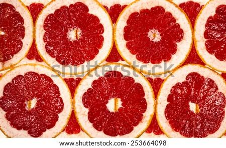 background of the many fresh grapefruit slices - stock photo