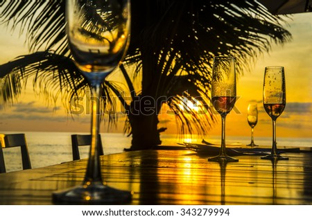 Background of three 3 glasses champagne vine staying on wood table chairs against palm silhouette sunset yellow sky with clouds couple in water on coast and sun light reflection on boards After dinner - stock photo