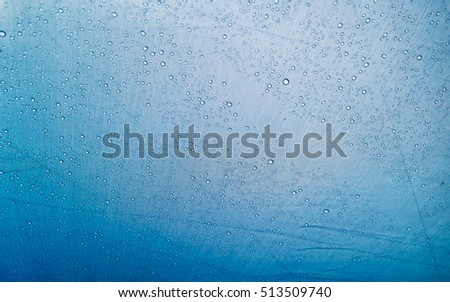 Background of tight blue fabric with water drops
