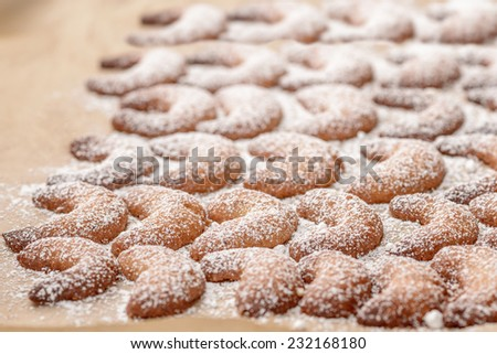 Background of traditional crescent shaped Christmas cookies or biscuits with crisp golden pastry sprinkled with sugar on a kitchen counter - stock photo