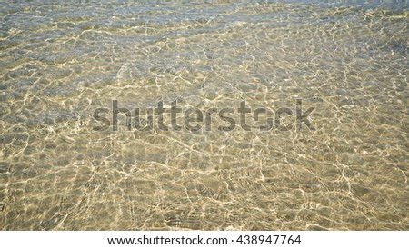 Background of transparent crystal green blue sea water surface ripple with sun reflection in summer. Water background. Ocean water texture. - stock photo