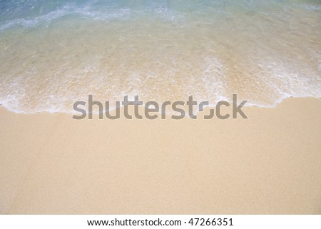 Background of tropical beach shoreline as wave runs up the sand. - stock photo