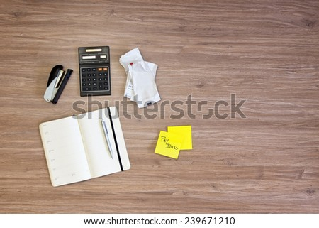 Background of various desktop items on a wooden surface. Items include a stapler, calendar, pen, calculator, some wrinkled bills, and a sticky note with the text Pay Bills written on one of the sheets - stock photo