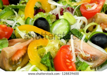 Background of Vegetable Salad with Tomatoes, Yellow Bell Pepper, Leek, Black Olive, Cucumber, Lettuce and Olive Oil closeup