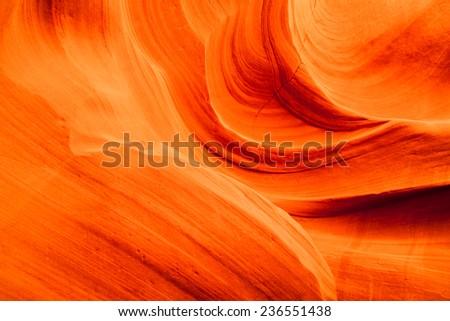 Background of vibrant orange swirling sandstone rocks inside of Upper Antelope Canyon in Page, Arizona. - stock photo
