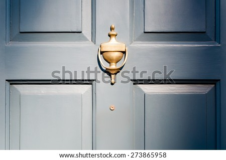 Background of vintage blue painted door and knocker vignette look - stock photo
