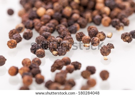 Background of whole fresh dried black peppercorns scattered on a white surface for use as a pungent spice and flavouring in cooking - stock photo