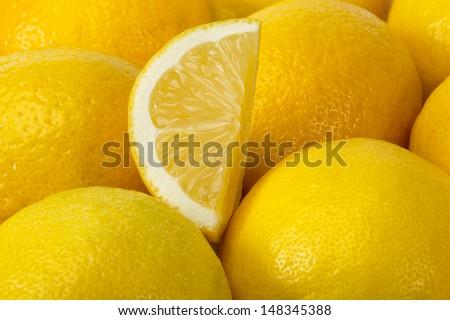 Background of yellow ripe lemons. A slice of lemon. - stock photo