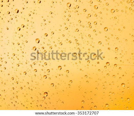 Background of yellow water drops on glass
