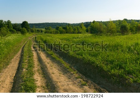 background picturesque landscape green field blue sky and wide country road disappearing into the forest - stock photo