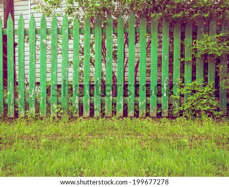 Background rustic wooden fence with green grass in front of it and tree - stock photo