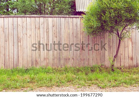 Background rustic wooden fence with green grass, road and tree in front of it  - stock photo