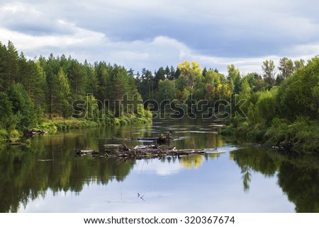 background scenery lovely little forest river with forest on the banks of the fall during leaf fall - stock photo