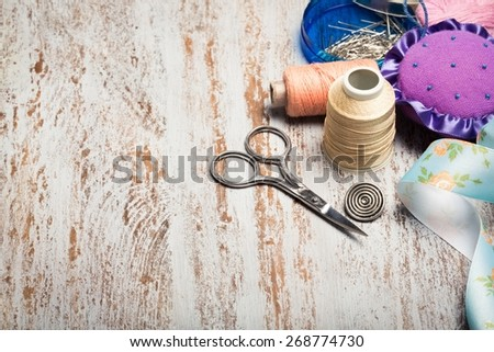 Background. Scrapbooking craft materials/ Background with sewing tools and colored tape/Sewing kit. Scissors, bobbins with thread and needles on the old wooden background - stock photo