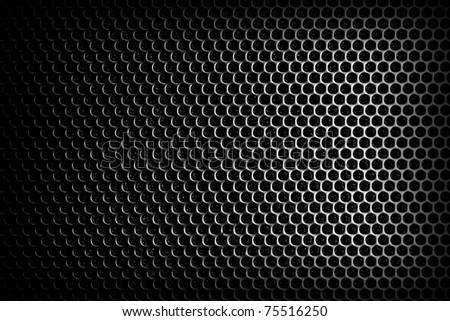 Background sheet of metal covered with lines of circular holes.