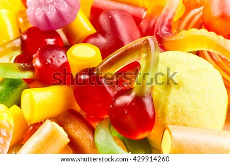 Background texture of a mixture of bright colorful jujubes and gummy candy in different shapes in a close up full frame view