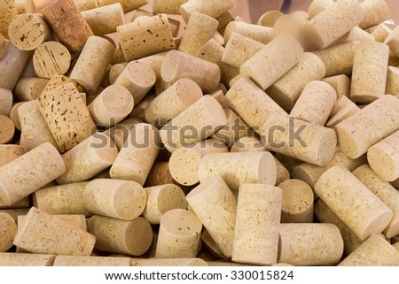 Background texture of a randomly scattered pile of assorted used wine corks with cultivar and winery details on the surface of the corks, close up overhead view - stock photo