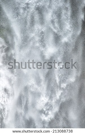 Background texture of a sheet of falling white water cascading down a cliff in a powerful torrent with spray on a mountain waterfall - stock photo