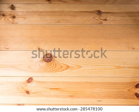 Background texture of a wooden table or floor with parallel planks with knots and a distinct wood grain pattern in a light wood, full frame - stock photo