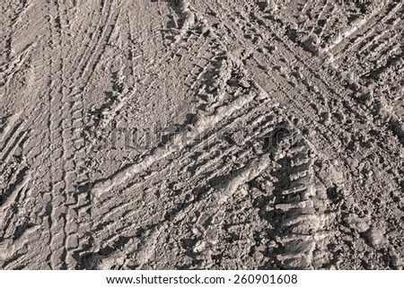 Background texture of dark brown road dirt with tire tracks  - stock photo