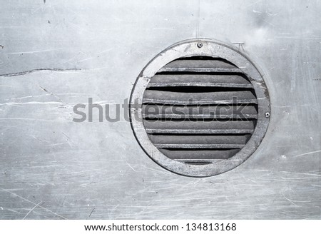 Background texture of metal wall with round ventilation element - stock photo