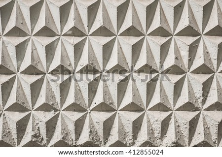 Background texture of old gray concrete fence with trigon pattern. Faded colors. Tiled. Sunset. Strong shadows.  - stock photo